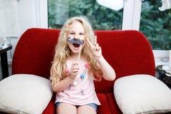Menina bonito com bigodes de papel ao sentar-se na cadeira vermelha em casa Foto de Stock Royalty Free