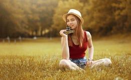 Menina bonito com a câmera no outono da grama Fotografia de Stock