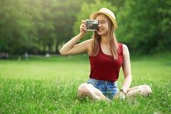 Menina bonito com a câmera no verão da grama Imagens de Stock Royalty Free