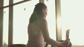 Menina bonito com cabelo longo no simulador no gym à moda, sol video estoque