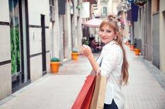 Menina bonito com chapéu e os sacos de compras que compram na cidade C fotos de stock