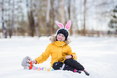 Menina bonito com coelho e cestas que sentam-se na neve para a caminhada Imagem de Stock