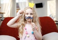 Menina bonito com coroa e os bigodes de papel ao sentar-se na cadeira vermelha em casa Imagens de Stock