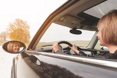 A menina bonito com corte de cabelo curto senta-se atrás da roda de um carro pequeno fotografia de stock