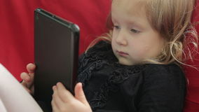 Menina bonito com desenhos animados de observação de uma tabuleta vídeos de arquivo