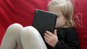 Menina bonito com desenhos animados de observação de uma tabuleta filme