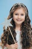 A menina bonito com expressão positiva, guarda a varinha, tem o cabelo escuro encaracolado, leva a varinha, acredita no conto de  fotos de stock royalty free