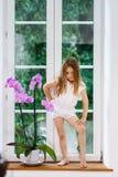Menina bonito com a flor que senta-se na soleira de wi novos do pvc imagem de stock