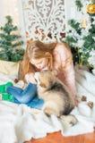 Menina bonito com jogos longos louros do cabelo com um cachorrinho pequeno do Malamute em casa foto de stock royalty free