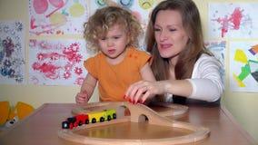 Menina bonito com a mãe bonita que empurra a locomotiva do trem do brinquedo na estrada de ferro vídeos de arquivo
