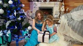 A menina bonito com mum olha e desembala um presente do Natal, embalado belamente na caixa de papel de envolvimento com uma curva filme