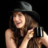 Menina bonito com o copo contra o fundo preto Imagens de Stock
