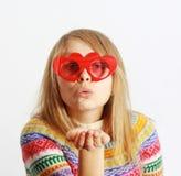 Menina bonito com o ki heart-shaped vermelho do sopro de vidros fotos de stock royalty free