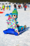 Menina bonito com os óculos de sol no trenó Fotografia de Stock