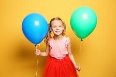 Menina bonito com os balões no fundo da cor Celebração do aniversário Fotografia de Stock
