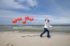 Menina bonito com os balões vermelhos na praia Fotografia de Stock