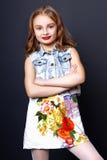 Menina bonito com os bordos vermelhos que levantam no estúdio Fotos de Stock