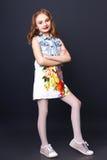 Menina bonito com os bordos vermelhos que levantam no estúdio Fotografia de Stock Royalty Free