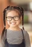 Menina bonito com os vidros que sentem felizes imagens de stock royalty free