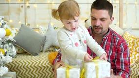 A menina bonito com pai novo desembala caixas de presente perto da árvore de Natal em casa video estoque