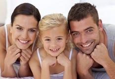 Menina bonito com seus pais que encontram-se em uma cama foto de stock royalty free