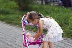 Menina bonito com seus transporte e boneca do brinquedo fora foto de stock