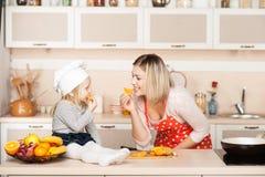Menina bonito com sua mãe que come a laranja quando Imagens de Stock Royalty Free