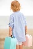 Menina bonito com sua mala de viagem no mar Imagens de Stock