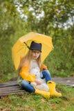 A menina bonito com um guarda-chuva amarelo senta-se em um trajeto na floresta com seu brinquedo favorito Fotografia de Stock Royalty Free