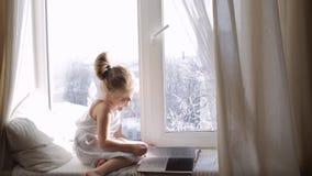 Menina bonito com um livro que senta-se no peitoril da janela inverno fora da janela video estoque