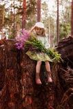 Menina bonito com um ramalhete das flores na floresta em um dia de verão Fotografia de Stock