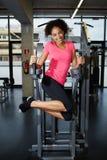A menina bonito com um sorriso bonito que dá certo para o Abs muscles no gym Fotos de Stock