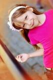 Menina bonito com uma aro em sua cabeça que anda ao longo do passeio imagem de stock royalty free