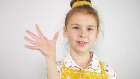 A menina bonito com uma faixa amarela e um avental amarelo faz um gesto do alimento delicioso Movimento lento video estoque