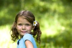 Menina bonito com uma flor em seu cabelo Fotos de Stock Royalty Free
