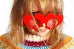Menina bonito com vidros heart-shaped vermelhos imagem de stock royalty free