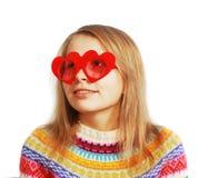 Menina bonito com vidros heart-shaped vermelhos no branco foto de stock