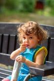 A menina bonito come petiscos no parque fotos de stock