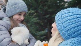 A menina bonito dá a sua mãe os mandarino e beijos da filha e da mãe filme