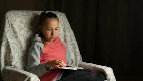 A menina bonito da criança na camiseta cor-de-rosa cinzenta senta-se na cadeira confortável na sala e lê-se o livro filme