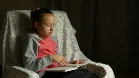 A menina bonito da criança na camiseta cor-de-rosa cinzenta senta-se na cadeira confortável na sala e lê-se o livro video estoque