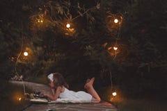 Menina bonito da criança no livro de leitura branco do vestido no jardim do verão da noite com decorações das luzes Imagem de Stock Royalty Free