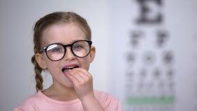 Menina bonito da criança nos vidros que tomam comprimidos para o tratamento da visão, vitaminas úteis filme