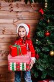 Menina bonito da criança pequena com as caixas de presente atuais perto da árvore em casa fotografia de stock royalty free