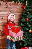 Menina bonito da criança pequena com as caixas de presente atuais perto da árvore em casa foto de stock