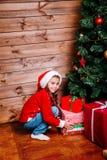 Menina bonito da criança pequena com as caixas de presente atuais perto da árvore em casa imagens de stock