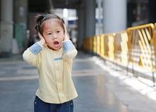 A menina bonito da criança pequena que interrompe suas orelhas, guardando suas mãos cobre as orelhas para não se ouvir imagens de stock