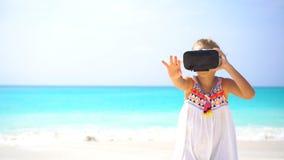 Menina bonito da criança pequena que usa óculos de proteção da realidade virtual de VR filme