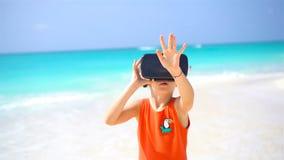 Menina bonito da criança pequena que usa óculos de proteção da realidade virtual de VR Olhar adorável da menina nos vidros virtua filme