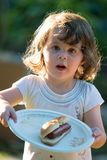 Menina bonito da criança que come o hotdog do cachorro quente imagens de stock royalty free